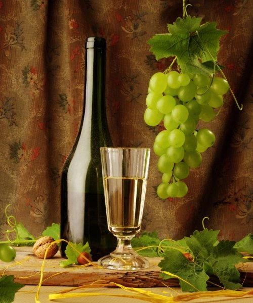 White wine with glass and grapes in background