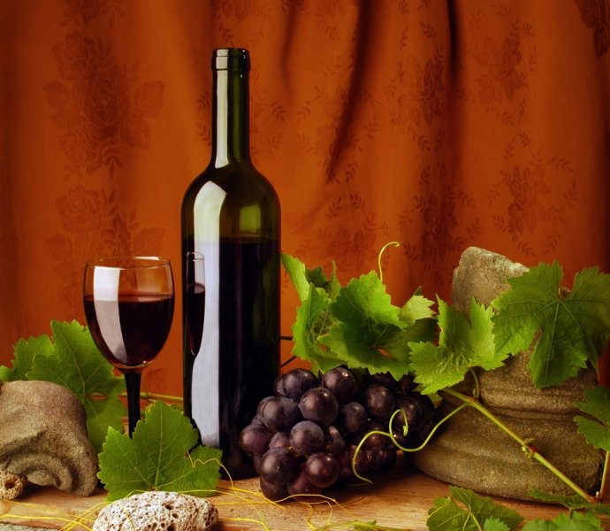 Red wine with grapes on table