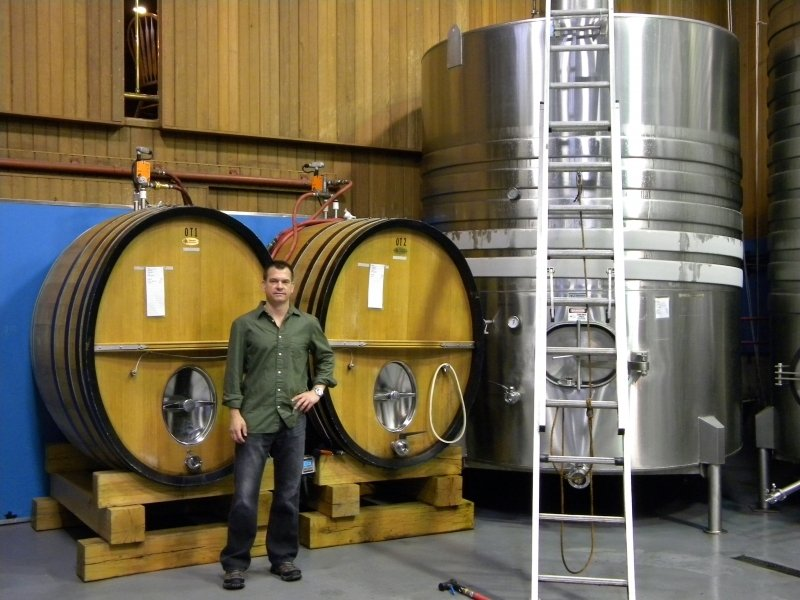 John standing next to barrels in Winery